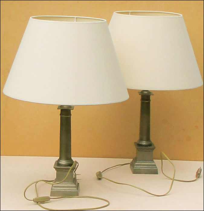 2 Classically shaped table lamps placed on a brass base