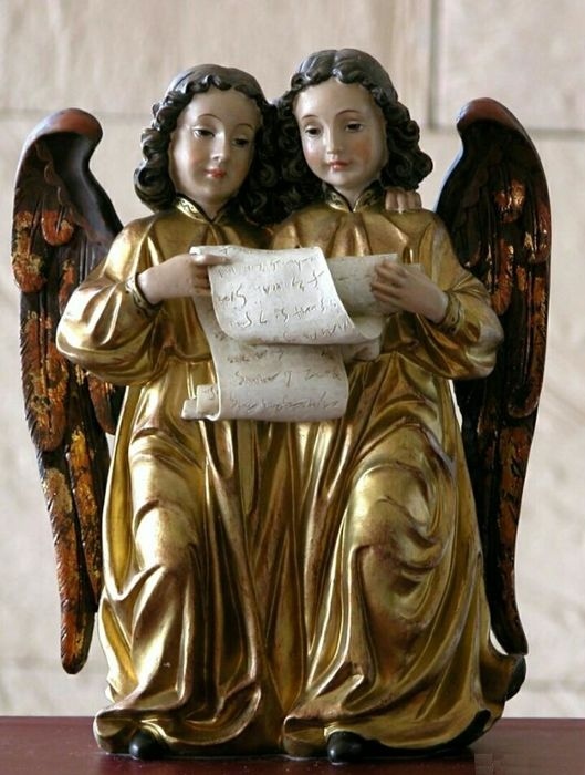 Extraordinary figure of two angels reading a parchment.