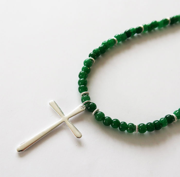 Necklace made of emerald gems, adorned with a silver cross.