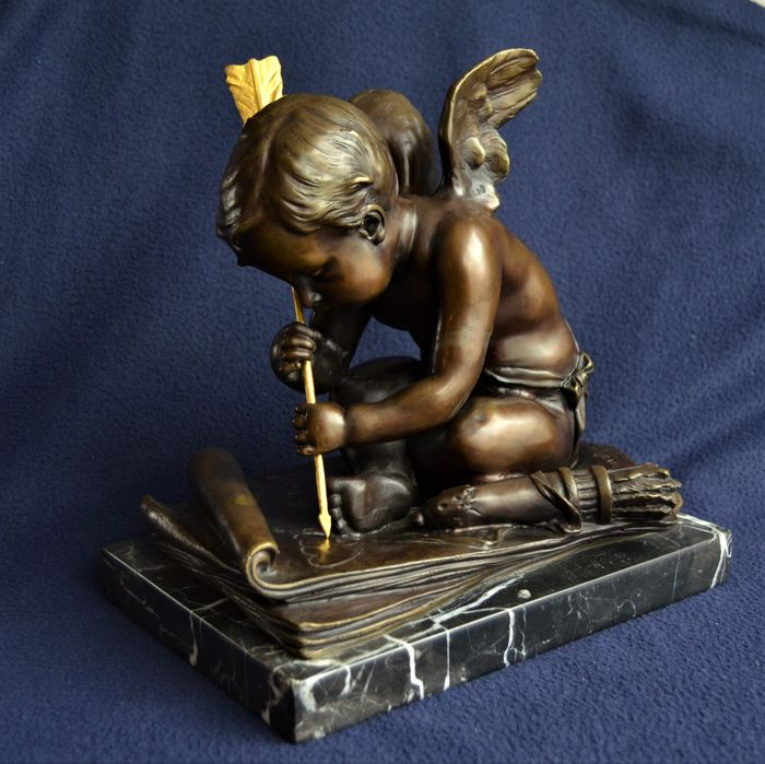 """A bronze """"writing cupid"""" on marble base."""