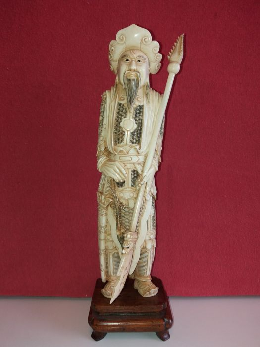 Sculpture depicting a warrior with a spear (temple guard), in ivory, on a wooden pedestal - China - 1900/1930