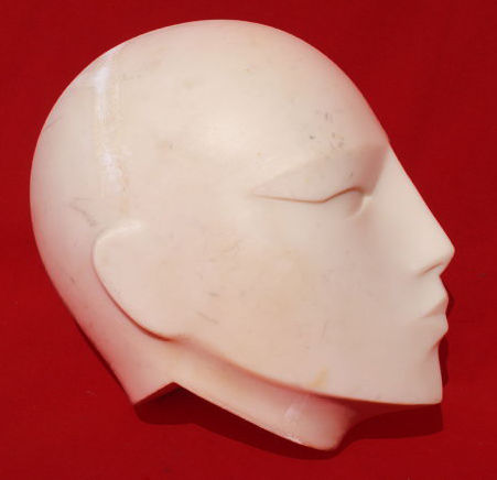 Ivory-coloured stylised head, marked J132