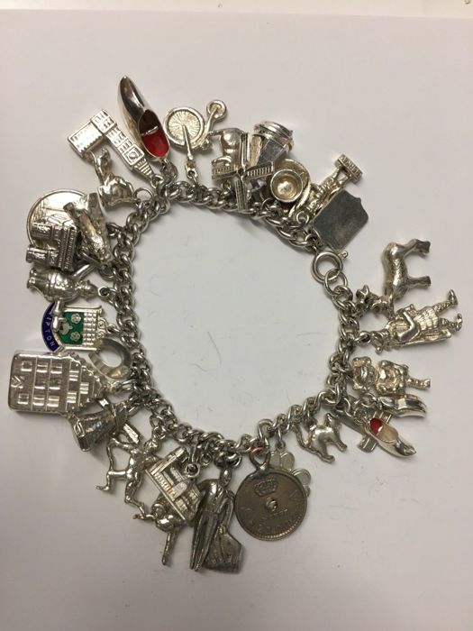 Vintage solid silver bracelet with 29 various charms. 67.4g. no reserve