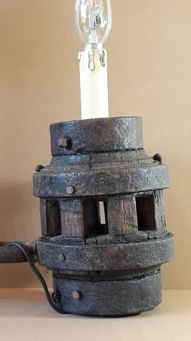 Striking wall lamp made from an antique pickaxe and the axle