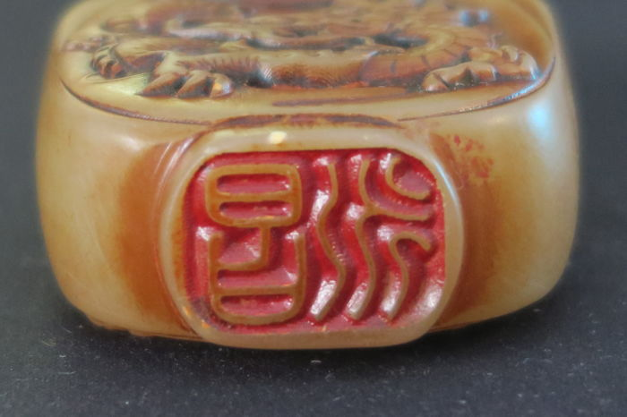 Snuff bottle with dragon carvings and seal stamps made