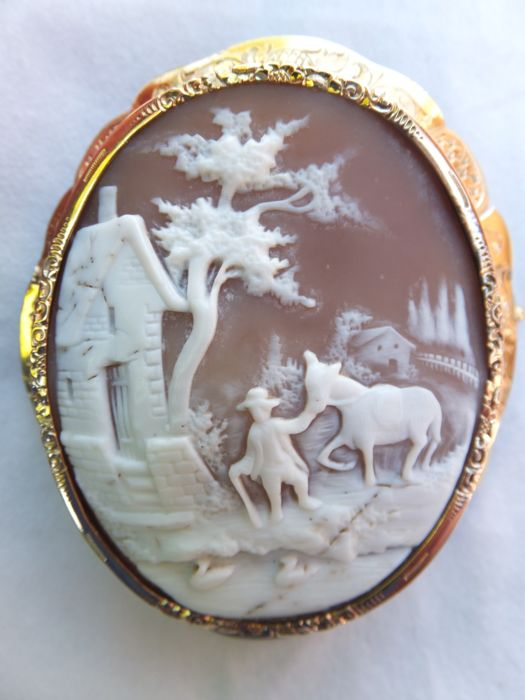 "A Shell Cameo Brooch, carved in superb quality,  ""Farm Scene""""  in a 14 carat 585/1000  (tested) golden frame. Italy round 1880."