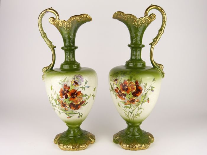 A pair of Victorian Rococo style gilt ceramic ewers