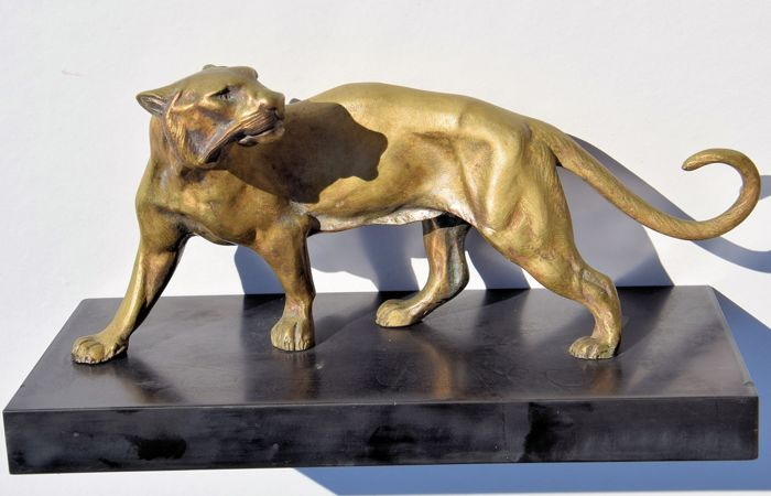 Bronze lion on a black stone base