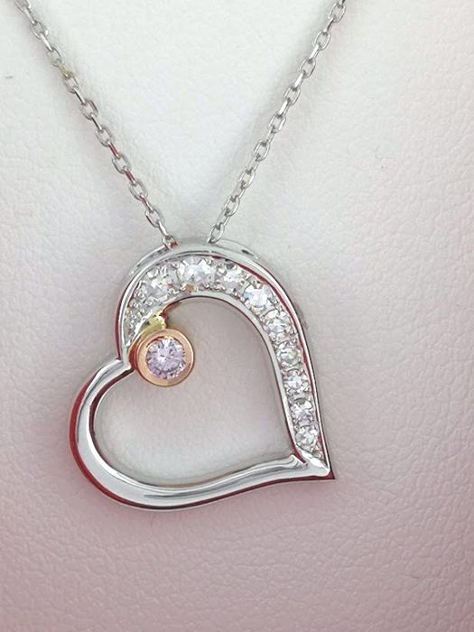Pendant in heart shape with a natural fancy pink diamond decorated with 9 diamonds 0.20 ct in total with a certificate by AIG. ***No reserve price***