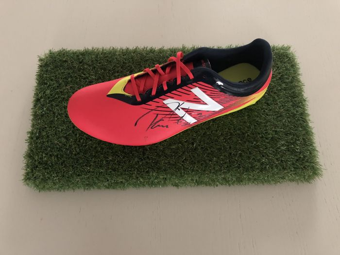 Paulinho signed New Balance football shoe on a mat of artificial grass with a photo of the signing and COA