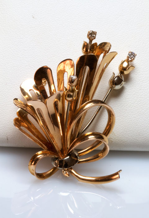 Elegant brooch in bow shape made of 18 kt yellow gold with diamonds of 0.15 ct