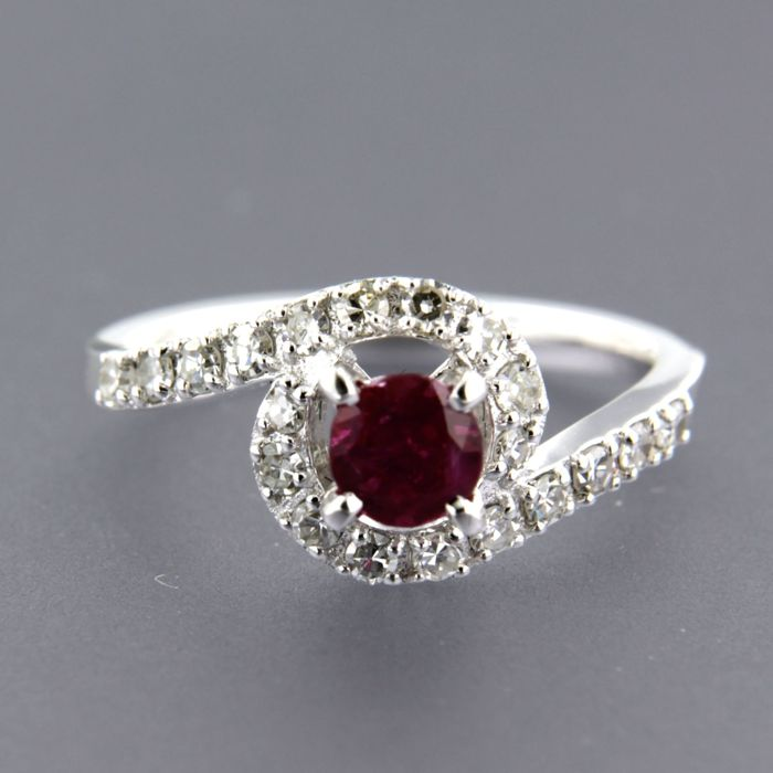 14 kt white gold wavy ring, set in the centre with a brilliant cut ruby and 20 single cut diamonds, ring size 16.5 (52)
