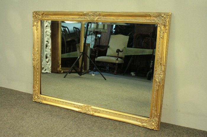 A large crystal mirror in a beautifully decorated wooden frame, covered with gold leaf flakes Poland