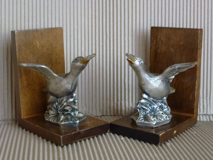 "Two bookends in silver metal with base in wood representing two geese with outstretched wings ready to fly - marked ""MM"""
