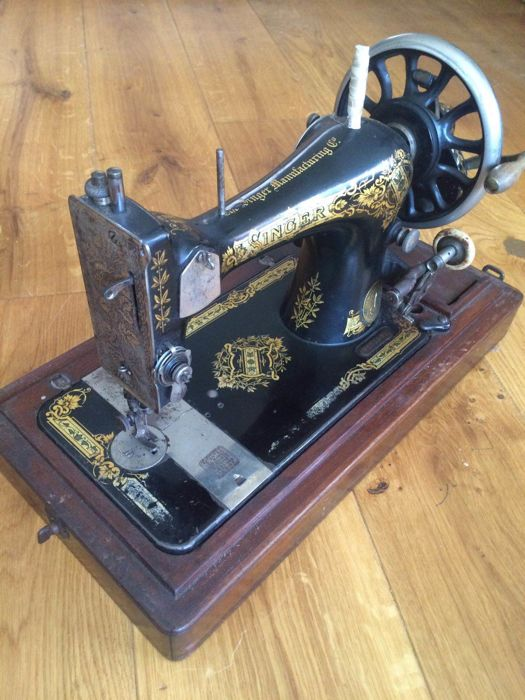 Singer 28 sewing machine with wooden dust cover, 1906