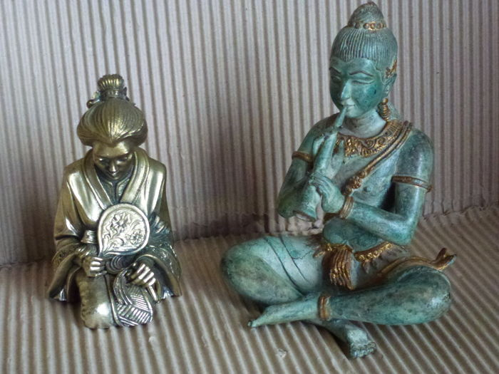 Two Asian statuettes: One from India, the other from Japan - cast bronze decorated and chiselled statuette of a Hindu divinity playing the flute - statuette of a Japanese geisha playing on her knees