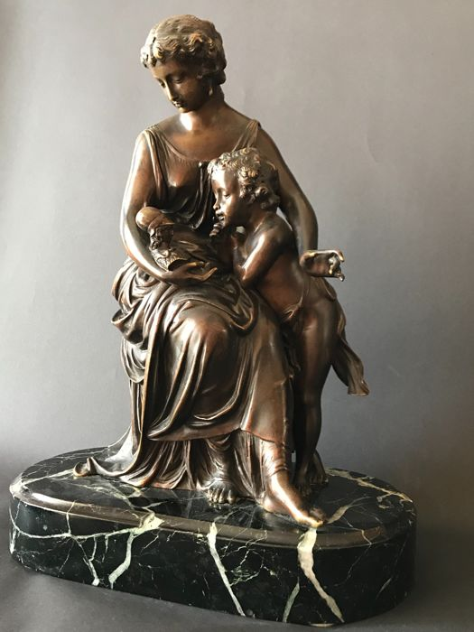 A well detailed bronze sculpture group of an elegant seated lady with a putto looking at a small bust - signed Moreau - France - second half of 19th century