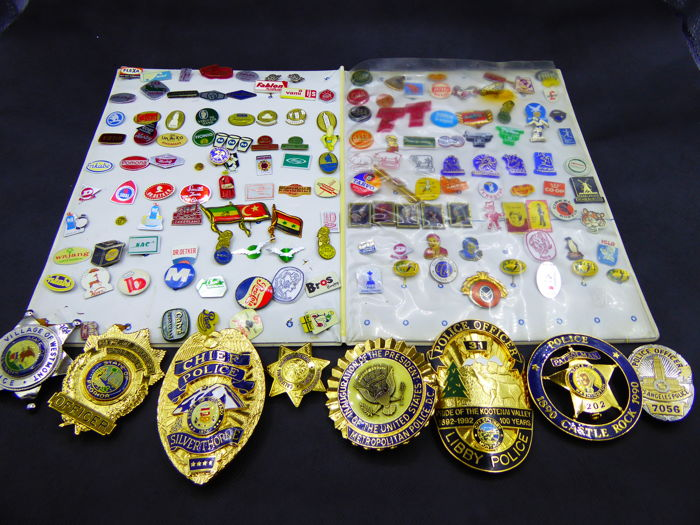 A collection of 145 pins and 8 replica police shields