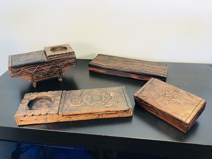 Four special wooden with hand -carved Balinese tobacco boxes.