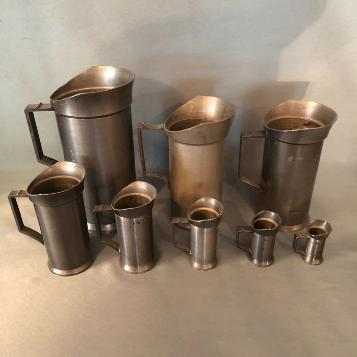 A set of eight pewter measuring cups