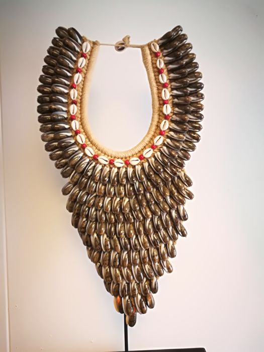 Large decorative necklace of shells placed on a metal stand - Southeast Asia