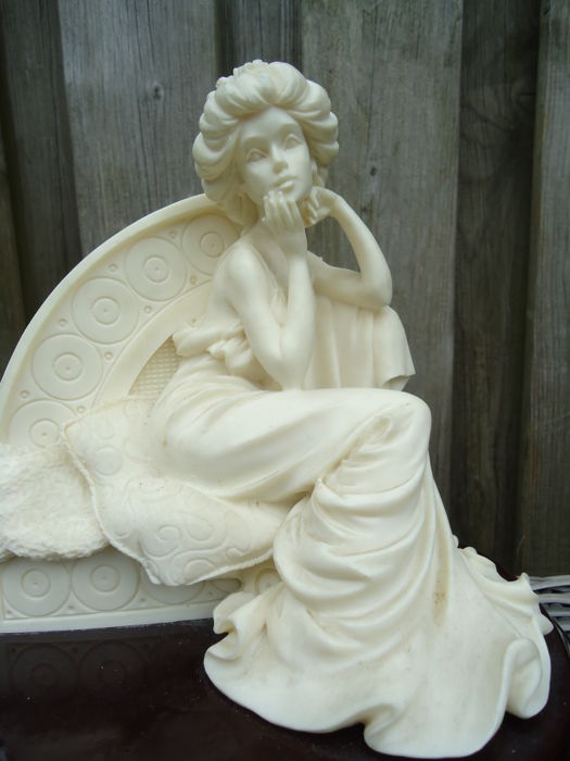 detailed Alabaster statue of an art nouveau-like Lady on a bench, on a varnished wooden base.