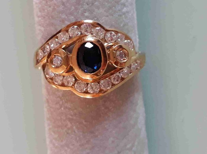 Ring in 18 kt yellow gold with oval brilliant cut central sapphire and accent diamonds  Ring size: 14