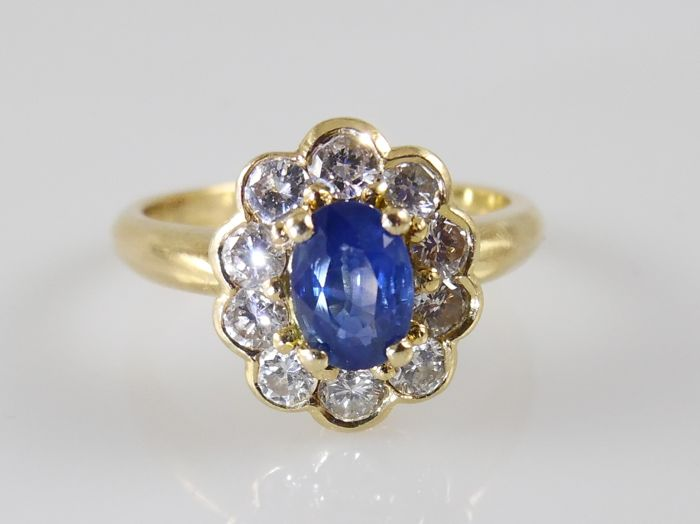 18 kt gold entourage ring with sapphire of 0.57 ct and 0.60 ct of brilliant cut diamonds, ring size: 52 (16.5 mm)