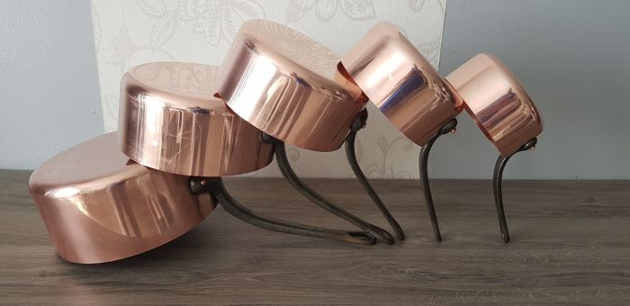 Set of five pans in thick copper with cast iron handle.