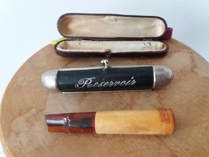 Antique art deco metal cigar storage tube with text Reservoir and cigar pipe in leather box.