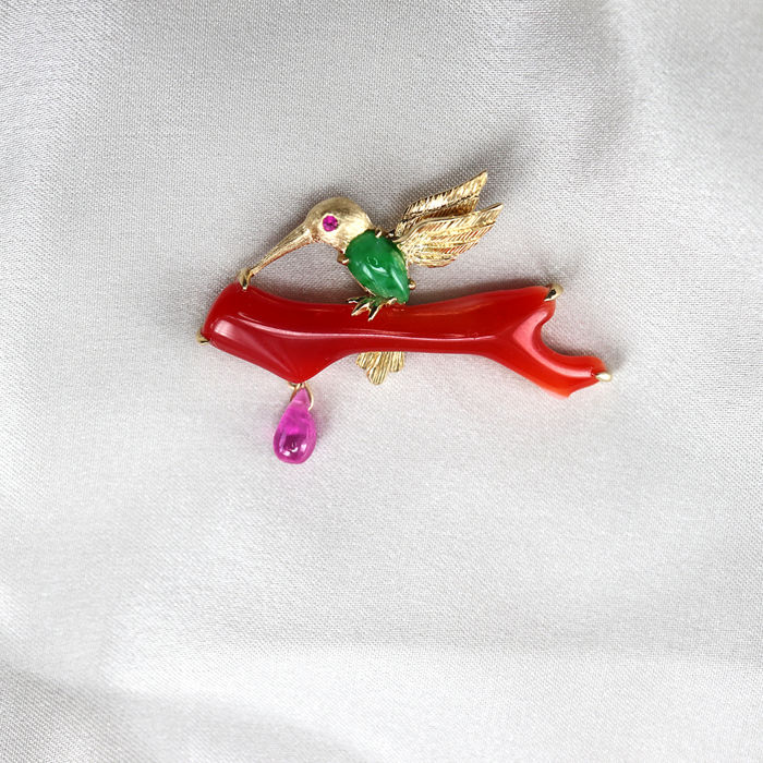 18Kt  pendant in the shape of a bird on a branch, set with 0.303ct of  Jadeite,  4.33 ct. of red coral (Aka) and 0.45 ct. of Ruby