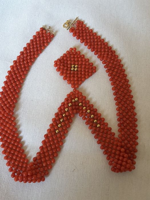 Sardinian red coral necklace consisting of interwoven threads with coral beads and a pendant attached to the necklace, with solid yellow gold beads that complete the design. Necklace length: 46 cm, pendant length: 4 cm.