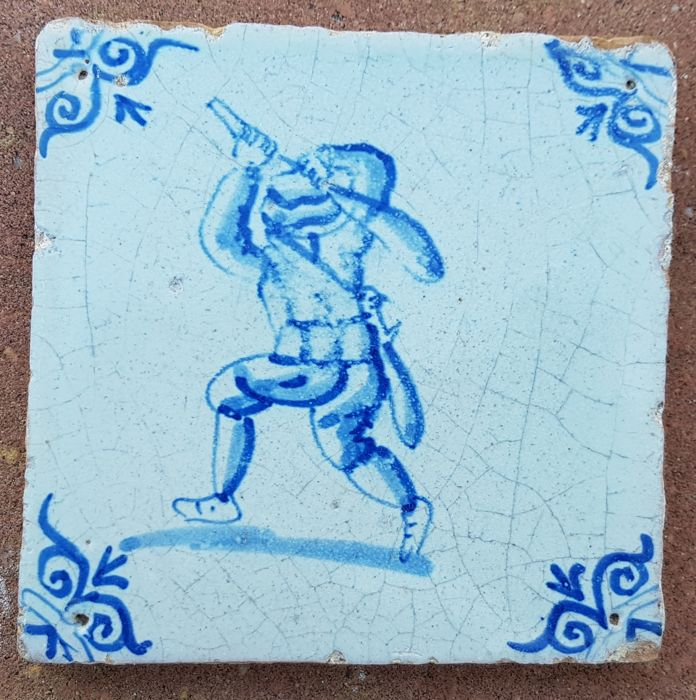 Tile with a soldier holding a club, oxen head corner motif - Holland - Ca. 1620-1640