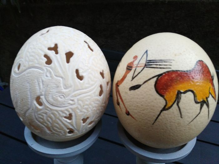 Two decorated ostrich eggs - painted in rock art with aurochs hunting scene, carved with a rhino and an elephant in full figure in the forest - 20th century