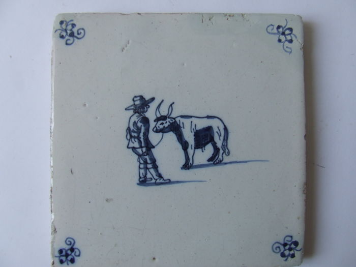 Antique tile with a farmer and cow