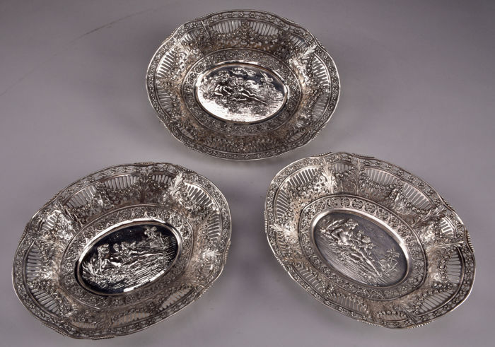"A set of three hand made silver fruit trays ""ALBO 835 HAND ARBEIT""- with romantic image of a half-dressed lady with putti - Germany, ca. 1900-1920"
