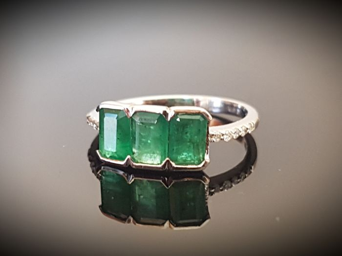 White gold diamond ring with an emerald trilogy
