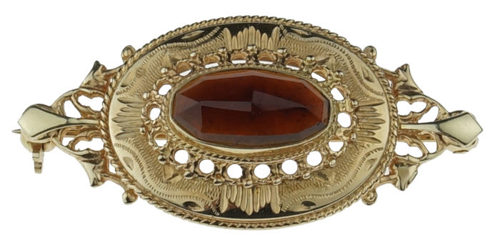 14 karat gold brooch with garnet in tooled setting