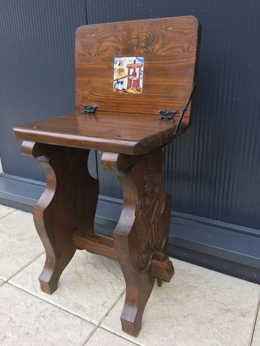 Antique heavy robust Spanish hand carved Castle Bodega wine cellar stool with folding armrest, knight in coat of arms engraving to the sides and in the centre a ceramic tile of a grapes presser