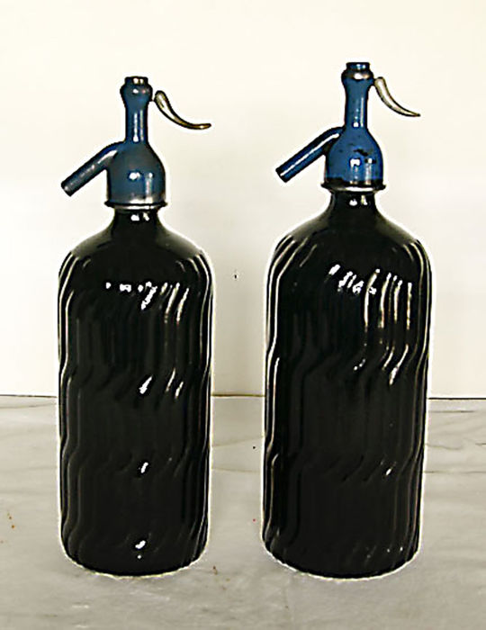 Two black Soda Seltzer siphons, modernist, with twin heads of lead