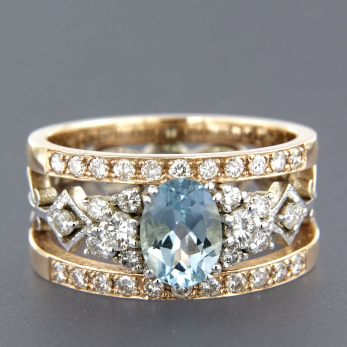 14 kt bicolour gold ring set with an oval cut sapphire of approx. 1.20 ct in total and an entourage of brilliant cut diamonds of approx. 0.75 ct in total