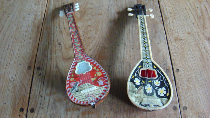 Two music boxes in the shape of a mandolin.