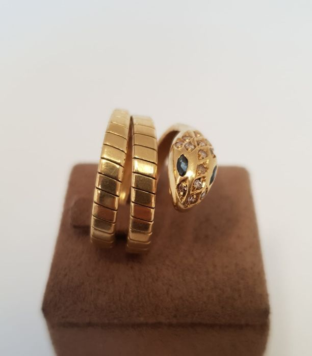 Flexible ring depicting a snake in 18 kt yellow gold, with diamonds and natural sapphire