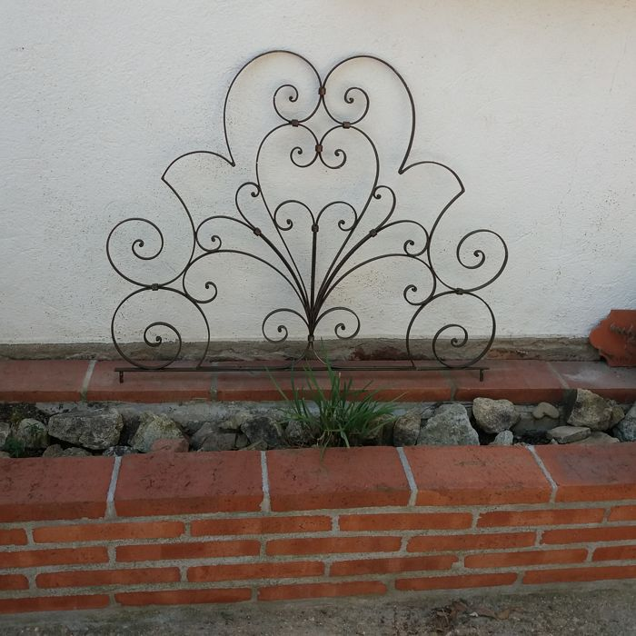 A decoratively curled hand-wrought iron ornament