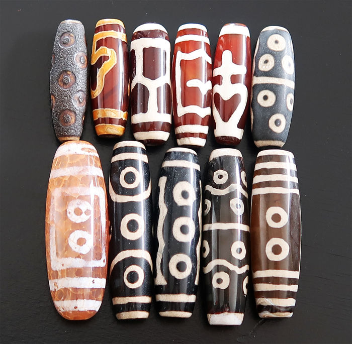 Eleven lucky charms in 'dzi' agate beads decorated with various patterns