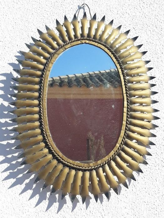 Large oval sun mirror in a golden frame for sale