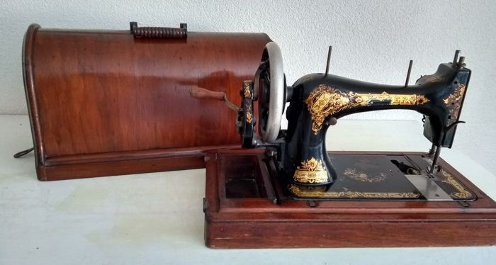 Singer 28 sewing machine with wooden dust cover, 1900