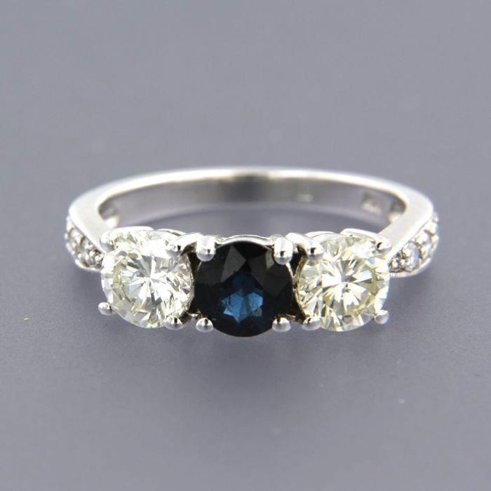 14 kt White gold ring set with a central brilliant cut sapphire of 0.60 ct, two brilliant cut diamonds of 1.10 ct in total and 6 brilliant cut diamonds on the shank of approx. 0.12 ct in total