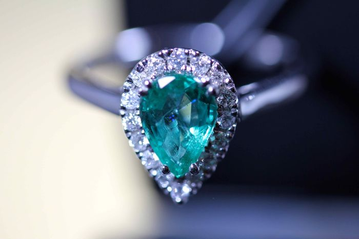18 kt white gold ring set with a 1.20 ct pear cut emerald and an entourage of diamonds with a sculpted basket stoned with diamonds for a total of 0.28 ct