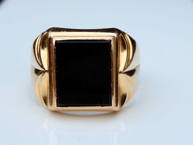 Ring in 18 kt gold with onyx on tooled shoulders